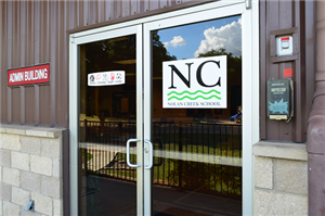 photo of the front door of the Belton Christian Youth Center with the NC log on the door.