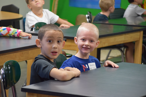 two boys on first day of school sitting at desk