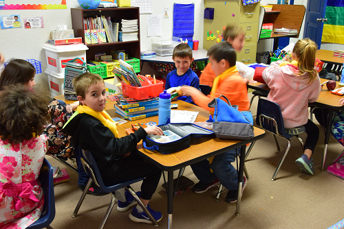 elementary students working in a group around a table