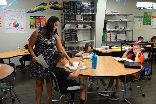 Teacher oversees work by students in classroom setting.