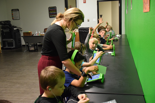 elementary students in computer lab with teacher oversight.
