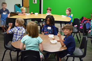 group of elementary students sitting at a round table