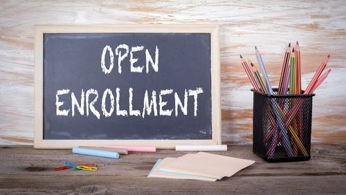 sign says open enrollment on bulletin board